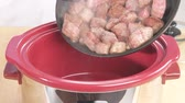 pot : Fried diced beef being added to a braising dish