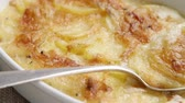potato casseroles : Potato gratin in a baking dish with a spoon (close-up)