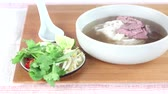 pasta dishes : Pho bo being served: stock being poured over rice noodles and raw and cooked beef