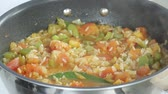 hotchpotches : A simmering rice and vegetable stew being seasoned with salt and ground black pepper