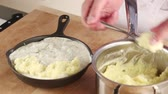 purê : Mashed potatoes being placed on fish pie ingredients