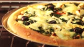фрукты : A spinach, sheeps cheese and olive pizza in an oven Стоковые видеозаписи