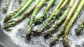 масло : Green asparagus being fried in a pan of butter