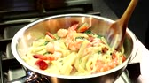 Ribbon pasta being stirred into prawns and cream sauce
