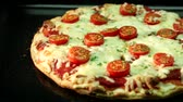 A pizza topped with mozzarella and cherry tomatoes baking in the oven