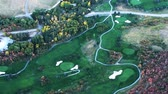 hráč golfu : Aerial shot of golf course. Grass is freshly cut and green. Golf course has pools and colorful trees. Pathways for golf carts are visible. Filmed during the day. Dostupné videozáznamy