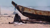 placa : Wide shot of woman cleaning fish in the shade of a boat on the beach