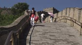 badaling : A shot of a woman walking down a steep decline at the Great Wall of China.