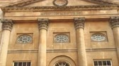 pilíř : Zoom out from a building facade with the words   and Corinthian column capitals. It is the Grand Pump Room in Bath, England.