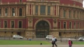 Лондон : Zoom out shot of Royal Albert hall as people and cars pass by in London