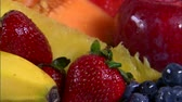 вещь : A close shot of an assortment of fruit rotating on a white screen.