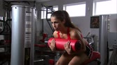 fitness : A woman doing sitting curls in a gym weight room Stock Footage