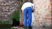inglaterra : Man sweeping off a stone patio next to a canal.