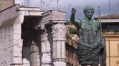telha : A shot of a statue of Caesar with buildings in Rome Italy in the background.