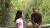 husband : Shot of a couple talking on a bridge Stock Footage