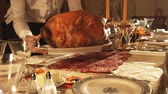 agradecimento : A woman serves a turkey at a decorated Thanksgiving table