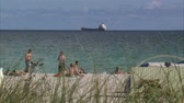 törülköző : A shot of a beach in Miami with people laying out. There is a cargo ship in the background.