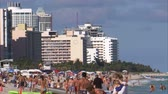 lefektetés : A shot of a beach in Miami with people playing in the ocean. There are hotels in the background.