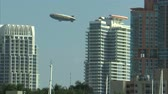 apartamentos : Shot of a Goodyear blimp appearing from behind a hotel in Miami, Florida. Stock Footage