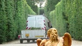 živý plot : Shot of a van pulling a trailer with branches between hedges with the top of a golden statue in the foreground.