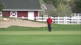 pim : A medium shot of a golfer on the green. He removes the flag and gets ready to putt.