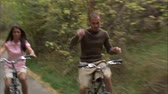 даты : A front moving shot of a couple riding their bikes through a tree covered bike path. The man rides with no hands.