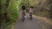 даты : A front moving shot of a couple riding their bikes through a tree covered bike path.