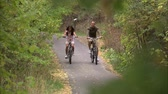 даты : A shot through the trees of a couple riding their bikes down a tree covered bike path.