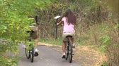 даты : A medium shot through the trees and from behind of a couple riding their bikes down a tree covered bike path.