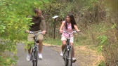 даты : A medium shot through the trees of a couple riding their bikes down a tree covered bike path. Стоковые видеозаписи