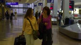 saco : Panning shot of two women as they walk through the airport after retrieving their bags at baggage claim in the airport. Others stand and wait in eh background.