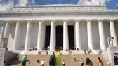 honra : Time-lapse of low angle shot of Lincoln Memorial in Washington D.C., with its tall, regal, Greek style architecture including white marble columns, with tourists and many people coming and going and observing below on front steps. Vídeos