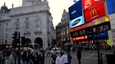 английский : Busy streets, buildings, and digital displays line streets filled with people at Piccadilly Circus in England.