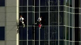 postroj : Two maintenance men wash windows in unison while hanging from the side of a skyscraper on a sunny day in Salt Lake City, Utah.