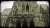 wiara : Tilt down on exterior of St. Stephens Cathedral, showing intricate gothic design of tall front and side walls, onto street below where people walk by. Vintage stylized video clip.