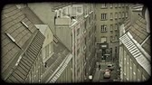 erkély : Tall European stylized apartment buildings, facing each other across narrow street and looking down at cars and a person walking in Vienna, Austria. Vintage stylized video clip. Stock mozgókép
