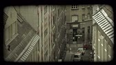 tabela : Medium shot above  tall European stylized apartment buildings, facing each other above narrow street with cars and a person walking in Vienna, Austria. Vintage stylized video clip. Stok Video