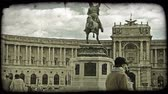 viyana : Shot of a statue in front of a building as people walk by in Vienna. Vintage stylized video clip. Stok Video