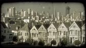 praça : Famous Alamo Square row of townhouses in San Fransisco with green manicured park and trees in foreground and busy San Fransisco downtown towering up in background. Vintage stylized video clip. Stock Footage