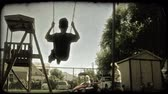 сбор винограда : Shot from behind of a boy as he swings on a playground swing with treehouse, little girl in play car, fence and parking lot in background. Vintage stylized video clip.