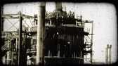 negócio : A tilt down from top to bottom of a Kuwaitee oil refinery. Vintage stylized video clip. Stock Footage
