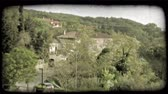 europa : Shot of an Italian town through some trees as some cars pass on the road below. Vintage stylized video clip.