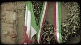 zeď : Shot of an Italian flag and ribbon draped wreath hanging on a wall in Italy. Vintage stylized video clip.