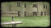 europa : Tilt down shot of a bench in a park in Italy to a large puddle on the ground. Vintage stylized video clip.