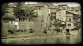 coberto : Pan left shot from a covered bridge the city buildings bordering the river. Vintage stylized video clip.