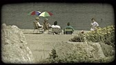 volný čas : Older couple sitting on beach chairs underneath colorful umbrellas on beach next to two women on beach chairs watch quiet lake front as girl wearing a tye dye shirt walkes toward flowers and large rock in foreground. Vintage stylized video clip. Dostupné videozáznamy