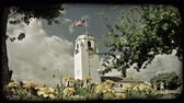 misja : People walk and play in distance next to tall mission church and American flag on pole with trees on sides and bright flowers on foreground. Vintage stylized video clip.