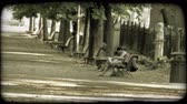 kordé : Two people relax on a park bench while others pass by on bicycles. Vintage stylized video clip.