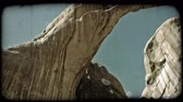 явление : Pan of two connected archs as they stretch above red rocks against a clear blue sky. Vintage stylized video clip.