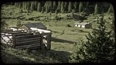 bosques : Slow zoom on old abandoned log cabin with no roof on rocky hill next to mountain valley with other old cabins by a mountainside filled with pine trees. Vintage stylized video clip.